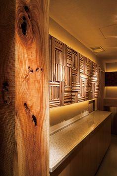 柱に使用した福島産のケヤキの無垢材は、切ってみたら虫食い穴が。それもまたひとつの物語として残すことに。カウンター奥の壁面装飾は、ブラックウォルナットの端材を短冊に切り、パネルに加工。