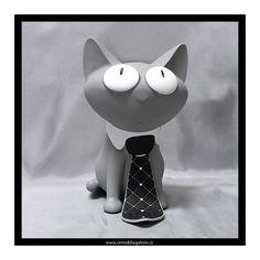 Pokladnička ve tvaru sedící šedé kočky s vykuleným pohledem, která je zdobená kravatou a límečkem. Kasička má pevné plastové provedení s polomatným vzhledem kůže, pokladnu lze vybírat díky šroubovací hlavě.