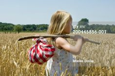 Stockfoto : Girl (6-7) standing in field carrying knapsack, side view