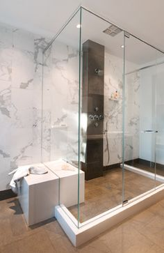 On the facing wall, a Caesarstone block creates a functional bench inside and outside of the glass-enclosed shower.