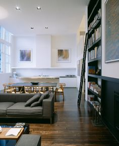 dark library wall, dark wooden floor + charcoal couch against white walls