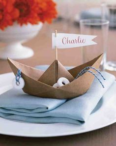 Set a shipshape table with seaworthy vessels whose sails designate guests' seats. These whimsical place cards require little more than kraft paper and a simple folding technique. Outfit boats with Life Savers candies and cast them adrift on blue napkins.