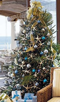 A beach Christmas tree. Palm fronds placed within; natural starfish and blue hued ball ornaments create the look.