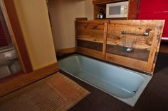 a regular bathtub layed into the deck with pallets reused to make a door cover.