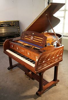 An Arts and Crafts Lipp grand piano for sale with a mahogany case inlaid in geometric designs at Besbrode Pianos. Case features ornate brass hinges.
