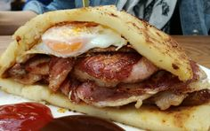 Sausage and bacon topped with a fried egg and served between potato bread. #sausage #bacon sausagebacon #egg #friedegg #bread #potatobread #foodfrique