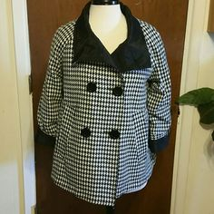 Jones New York reversable coat One side is a black and white hounds tooth, the otherside is black. Button up on either side, has pockets and cuffs. Made of acrylic, polyesther and wool. This proced valuable as it was rainy and cold, and I was flooded ! So I put the black rain ciat side out and the houndstooth (wool) in. Stayed warm and dry. Jackets & Coats