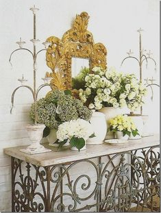 gorgeous vignette by Houston, TX designer Carol Glasser -  ornate, gilt mirror, above wrought iron console table |  floral display