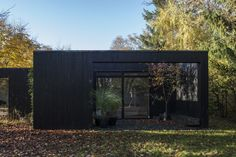 A black wooden house surrounded by nature
