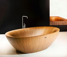 A lighter colored wood choice by Alegna makes this wooden bathtub no less appealing.