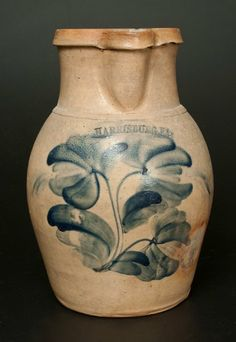 "Lot Passed Estimate $2,000 – $3,000 Rare and Fine Stoneware Pitcher with Elaborate Cobalt Floral Decoration, Stamped ""HARRISBURG PA,"" probably William Moyer, circa 1858, ovoid pitcher with pronounced rim molding, the front decorated with a large flowering plant bearing three tulip blossoms. Impressed below spout with early ""HARRISBURG. PA"" maker's mark, often attributed to William Moyer. Additional cobalt highlights to maker's mark and handle terminals. Pitche"