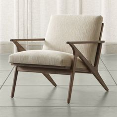 Relax back to another modern time.  Cavett's mid-century lines capture the best of 1950s design in solid American walnut and cushioned seating upholstered in  a warm, textural weave with a hint of retro character.  Dramatic streamlined arms, cantilevered seat and vertical slat back attract the eye from every angle.