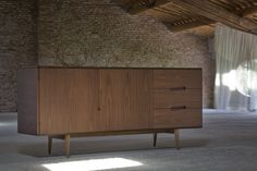 MALIBU, made of canaletto walnut with two doors and three drawers. Particular diagonally inlaid handles and legs with triangle section