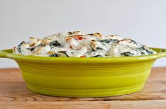 Kicked-Up Spinach Dip  makes about 3 cups of dip  8 ounces (1 block) cream cheese, softened  8 ounces sour cream  1/2 medium sweet onion, chopped  1/4 red pepper, chopped  1/4 green pepper, chopped  1/2 cup chopped mushrooms  2 cloves garlic, chopped  1 bag spinach  1/3 cup crumbled blue cheese (or cheese of your choice)