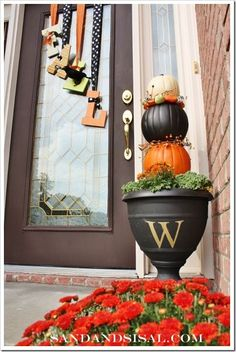 "Personalized Pumpkin Topiary and ""FALL"" Letters hanging from holiday ribbon on front door."