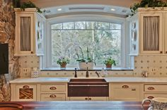 Happy Hollow: A Gambrel-Style House & Guest Cottage 125 Rockwood Brookline MA  Gourmet kitchen Copper fixtures including farm house copper sink with a beautiful view through the large/deep window over the sing.