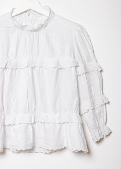 White linen embroidered blouse with ruffled detailing throughout. Standing frill collar, with strategically placed layers of ruffles at the chest, sleeves, and