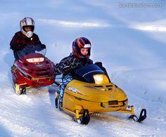 """Kinder fahren Schneemobil im Schneemobilpark namens """"Arctic Circle Snowmobile Park""""  in Rovaniemi"""