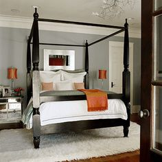 Gray is the ultimate neutral. It looks good with almost any color and ranges from cool to warm. In this bedroom a classic gray coats the walls. A black four-poster and cream-color shag rug complement the cool wall color. Burnt orange accents, table lamps, and throw pop in this neutral room. A mirrored nightstand and metal-framed mirror above the bed add a touch of glamour.