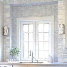 Absolutely stunning kitchen scene featuring a pair of Jennings sconces designed by Libby Langdon for Crystorama!  #wallsconces #kitchenwindowideas #marbletilebacksplash #kitchenlighting #designerlighting