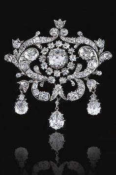 An antique diamond brooch, mid-19th century. The central old-mine diamond in a cut-down collet within openwork surrounds, designed as foliate scrolls, set with old-mine diamonds, suspending three pear-shaped diamond drops. #Antique #brooch