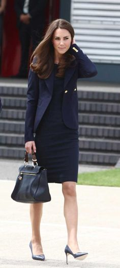 At the Heathrow Airport, before departing for Canada, Kate wore a navy blue  Roland Mouret dress with and a navy Smythe les Vestes blazer.  She topped off her outfit off with a Mulberry Handbag and blue court shoes.
