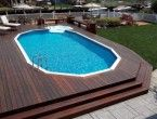 Contemporary oval above ground pools with dark brown wooden decks