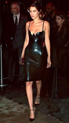 BELLA HADID Second-skin black latex with a tiny chain-strap bag and Christian Louboutin spike heels.