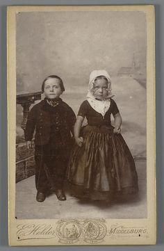 Jongen en meisje in Walcherse streekdracht, omstreeks 1900. Het meisje draagt onder de muts een ondermuts met een oorijzer. Aan de 'krullen' (oorijzeruiteinden) hangen klaverbladvormige oorijzerhangers met een parel, de 'strikken'. #Zeeland #Walcheren