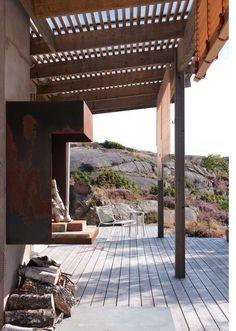 HETT SAMLINGSPUNKT: Peisen i stål er tegnet og bygget av beboerne selv. Skjelettet i stål er sveiset sammen og hektet direkte på pipeløpet. Innvendig er den også stålkledd, bunnen er dekket av murstein. Den vakre rustne fargen kom helt av seg selv etter et par sesonger, det sørget de salte havvindene for. Peisen krager ut fra veggen og er festet relativt høyt på pipa, siden den også brukes som grill. Spilene i pergolaen skjermer mot solen, glasset over sikrer en tørr sone langs veggen. Den…