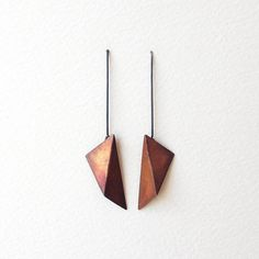 Hand fabricated metal is folded and assembled into geometric earrings. The dandle triangles are made of different materials and finished in two