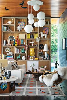 The site-sensitive exterior belies an interior festooned with a kaleidoscopic mix of colors and an array of tactile materials. The Peter rug, Malibu sofa, and ceramics are Adler's own designs. The tables, pendant lights, and rocker are vintage. Adler and Doonan used scaffolding from the house's construction to build the bookshelf.  Photo by: Floto + Warner