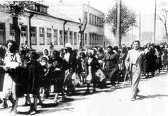 """A column of Jewish women and children begin their death march guarded by Lithuanian """"self-defense"""" irregulars working with the SS. Note the expression of the woman leading the column. Next to her is most likely her daughter. The mother at least appears to know what is store for them in the next few hours. The massacre of the innocents by the permanently guilty. 1941."""