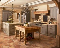 Unique combination of styles for a great result - tile floors, grey cabinets, brick back splash and columns, wood trimmed range hood and arches, butcher block island Coastal Va Magazine's Best Kitchen & Bathroom Remodeler #dogoodwork www.jimhicks.com