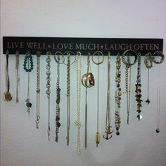 Do-it-yourself jewelry organizer slash wall decoration: wood plank with wall mounts from Target, brass plated 'cup hooks' from Home Depot, jewelry from your collection :)