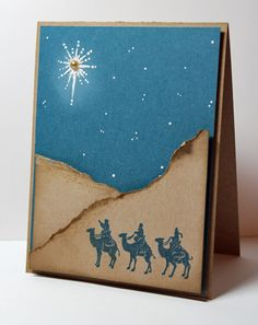 By Deb. My plan: Tear tan paper for sand dunes. Sponge top edges. Stamp 3 Kings on one dune. (Deb used Memento Nautical Blue.) Attach to blue cardstock panel. Stamp main star in on the blue panel with white pigment ink. Use white gel pen for other stars. (Deb used Hint of Violet Glitter Frosting instead.) Add pearl or gem in center of main star.