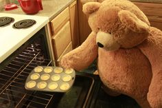 Big Hunka Love Bear putting Valentine's Day cupcakes in the oven.