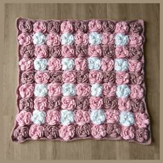 The Gingham Flower Blanket can be customized to make the blanket any size desired by increasing or decreasing the number of flowers made. The blanket will be thick and heavy. While not ideal for wrapping up a baby, it would be beautiful at the end of a bed, or if made larger, this would make a gorgeous, thick, warm comforter. The blanket can be used as plush rug or for a unique photography prop.