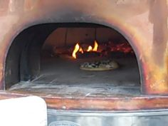 Cooking a pizza in a wood fired oven