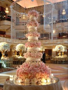 Light Pink & White Wedding Cake...to die for...love the center pieces in the back on the tables too!