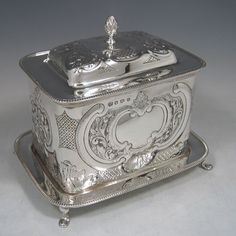 Sterling silver large hand-chased biscuit box with attached plate, made by William Hutton of Sheffield in 1930.