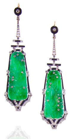 A pair of jadeite jade, enamel and diamond pendant earrings,   designed with jadeite plaques carved as fruiting vines with gourds, highlighted by rose-cut diamonds, onyx and black enamel accents; mounted in platinum and eighteen karat gold; length: 3in.  Via Bonhams.
