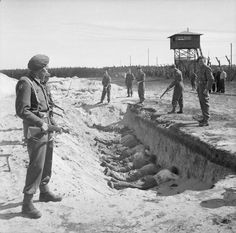 German SS guards, exhausted from their forced labour clearing the bodies of the dead, are allowed a brief rest by British soldiers but are forced to take it by lying face down in one of the empty mass graves 1945