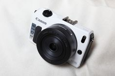 A white Canon EOS M with a 22 mm f/2 lens.