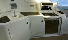 Sea Ray 540 Sundancer: Under the grill is a standard ice maker. Note the counter space and trash container hidden at left.