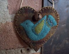This cute little heart would look so cute anywhere in the house as an accent to your decorating! I have left an opening at the top to put in a tuft of greenery or sprigs of lavender, or even a little note and some candies for your valentine!  The heart is made of wool felt. I used jute twine for the hanger. I have included a little rusty bell for accent.  This little heart measures about: 3.5 by 3.  Spot clean only.