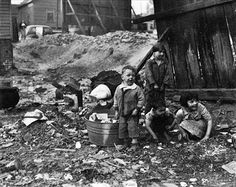 Depression era children in a slum section of Fair Street, Atlanta, GA playing among the trash and debris of the slums, their only place to play.  Date : Apr, 1936  Agency : WPA, Owner : NARA (SPB)