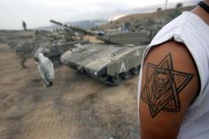 An Israeli army reservist, who sports a tattoo of a lion surrounded by Star of David, works on his tank as another performs his morning prayers at a forward base where the Israeli army have deployed dozens of tanks and armored vehicles, near Israel's border with Lebanon 08August 2006. Two Israeli army reservists were killed today in clashes with Shiite militant group Hezbollah in south Lebanon, the army said. The deaths brought to 63 the number of troops killed since Israel launched its offensiv
