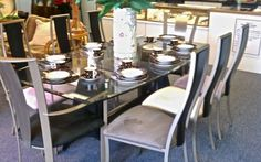 Stunning modern dining table and 8 chairs made of glass and metal. $1050 Available at Board of Trade Sarasota Fine Consignments.