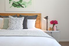 Master bedroom funky styling banana leaf print grey linen euro spotted cushion moss green cushion matte black lamp